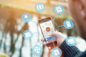 smart house, home automation device illustration with app icons. Man holding his smartphone with smart home automation app in his hand. The internet of things makes it possible to remote control his entire house with his mobile phone from around the world.
